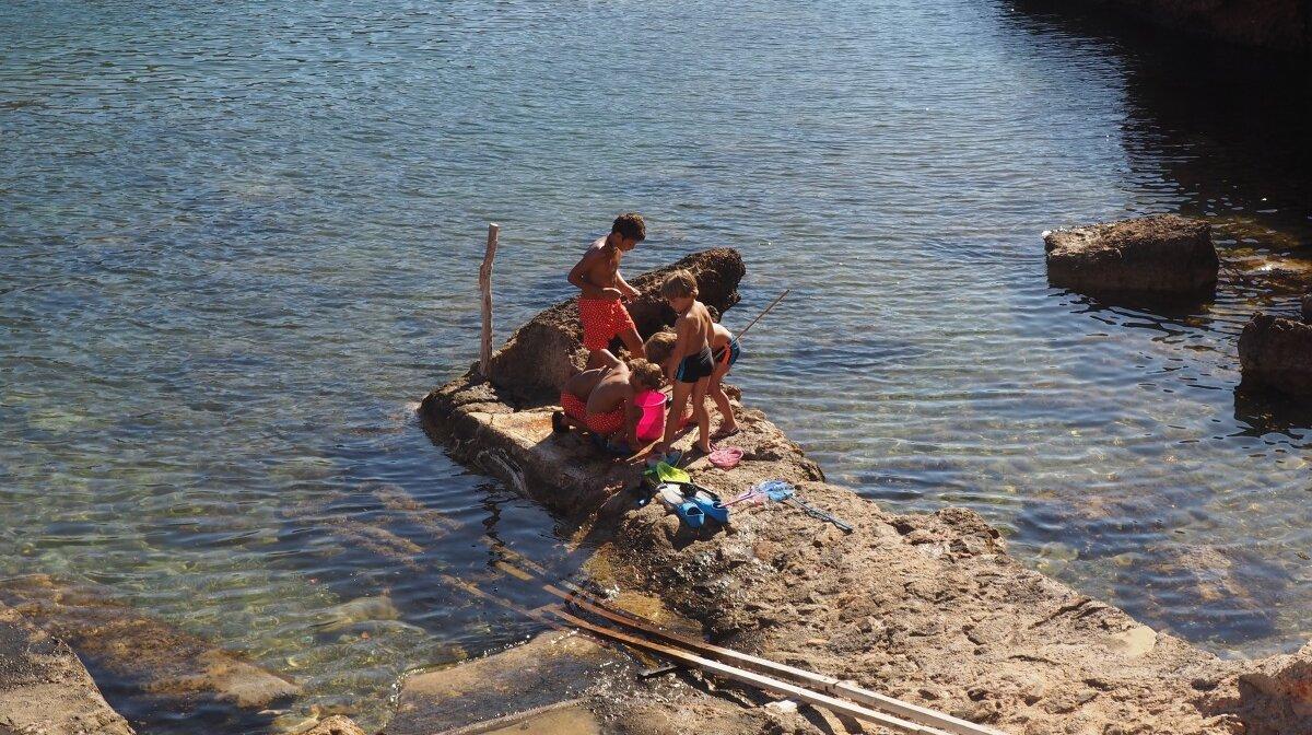 young boys fishing off the coast at cala corral