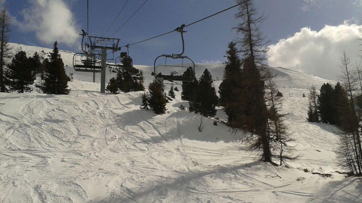 a chair lift going over some snow and trees