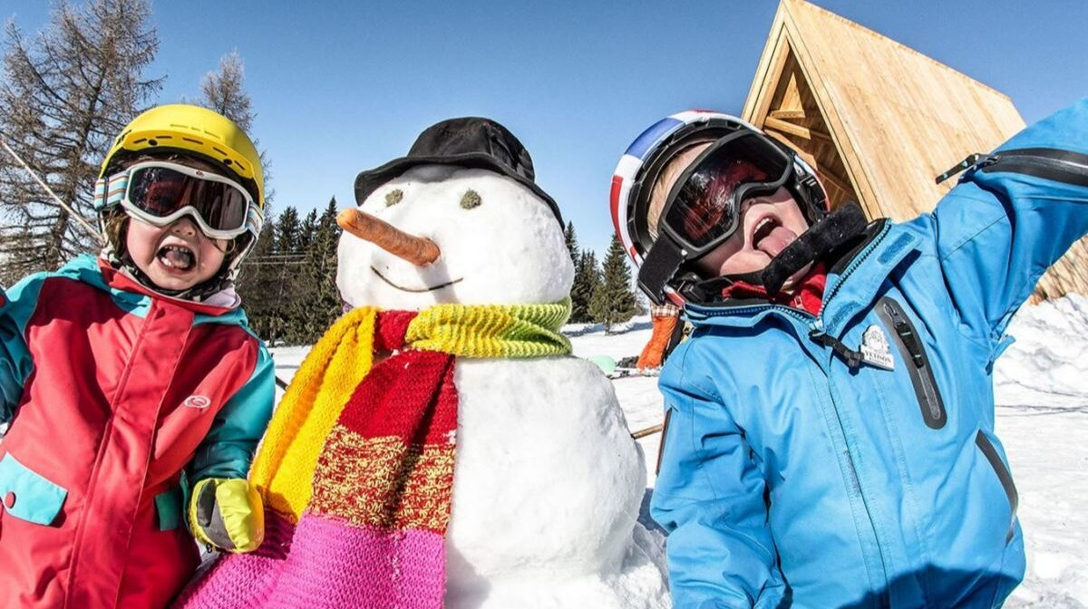 children with a snowman in les arcs