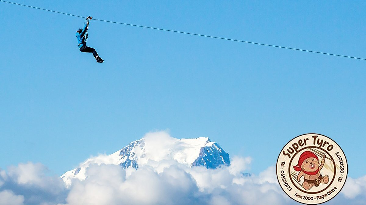 a person on a zipline high about the ski resort of la plagne