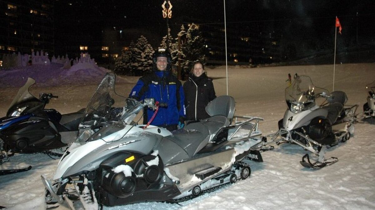 a couple with a snowmobile at night
