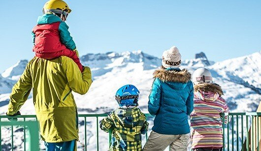 a family looking at the snowy mountains