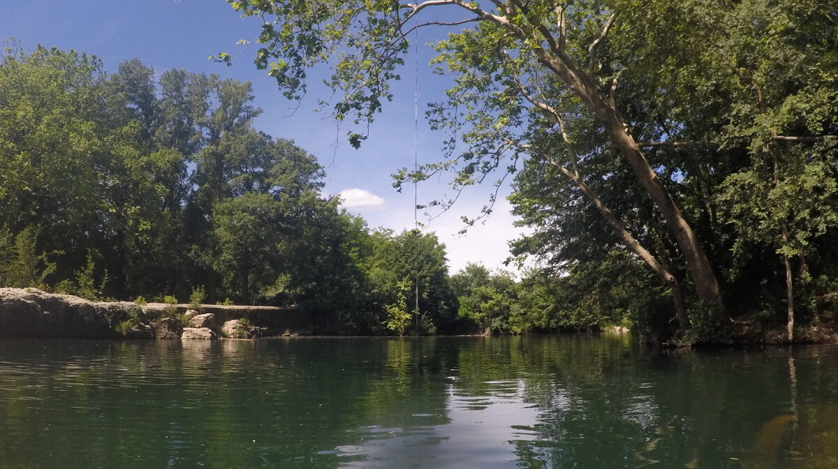 the rope swing at a swimming pool on the river ceze in provence
