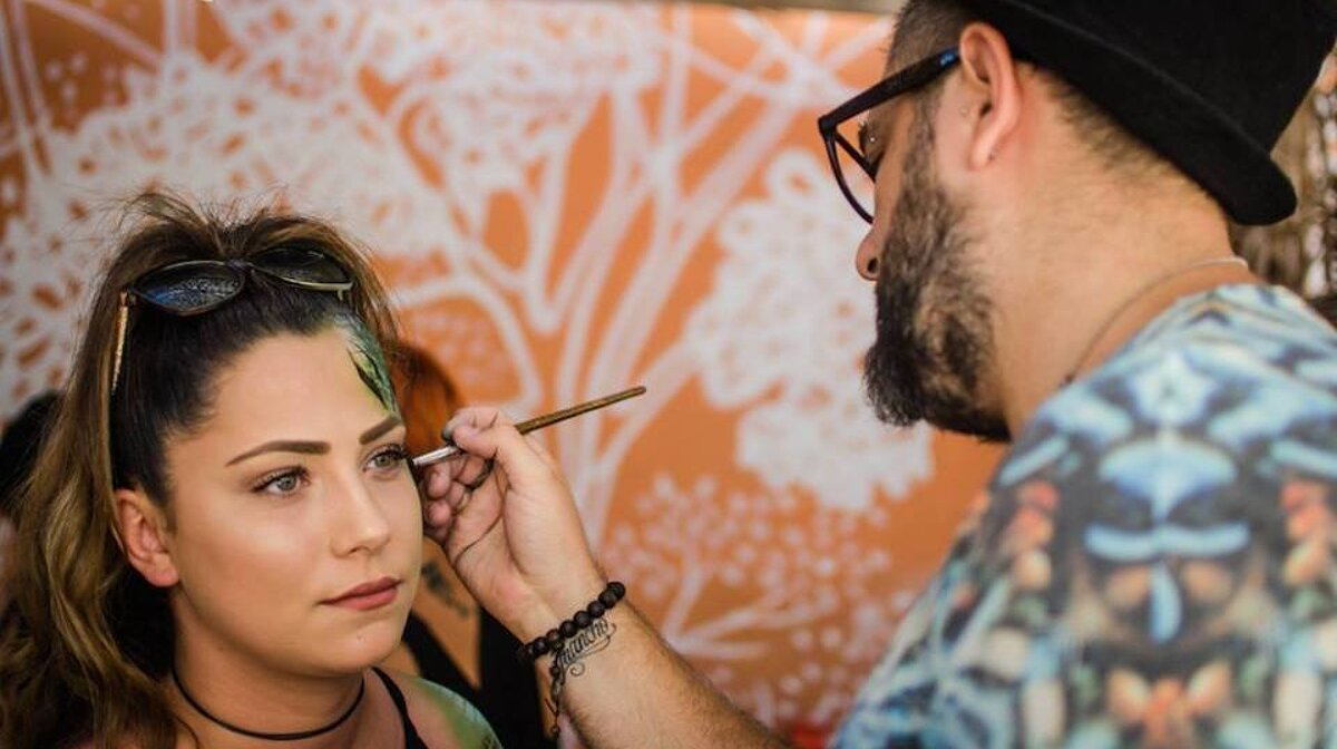 a girl getting facepaint on at the zoo project san antonio ibiza