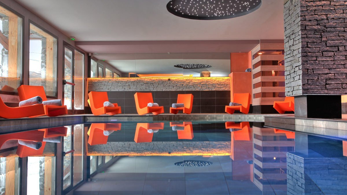an indoor swimming pool with orange chairs around the sides