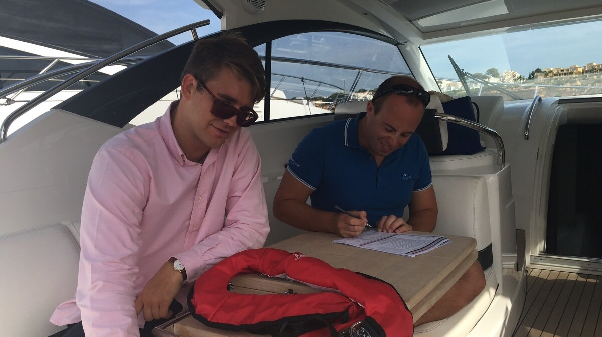 two men on a motor boat doing a theory test for ICC