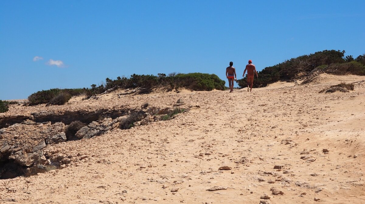 a couple of people hiking in the sand dunes of south ibiza
