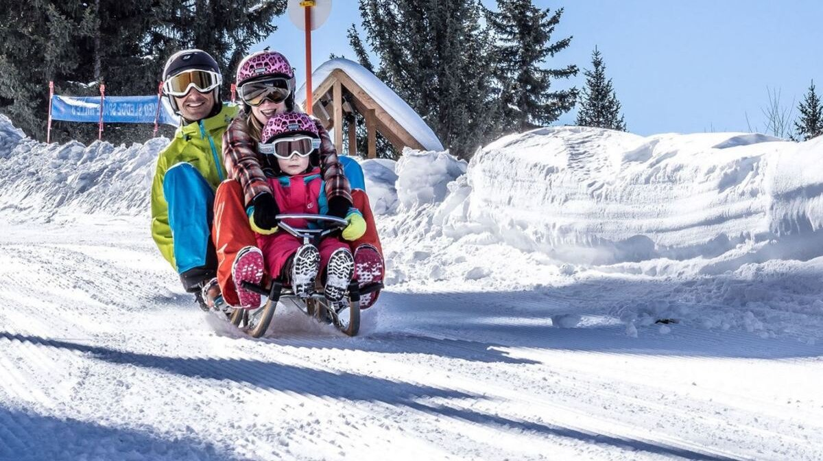 a family on a sledge at mille 8 in les arcs