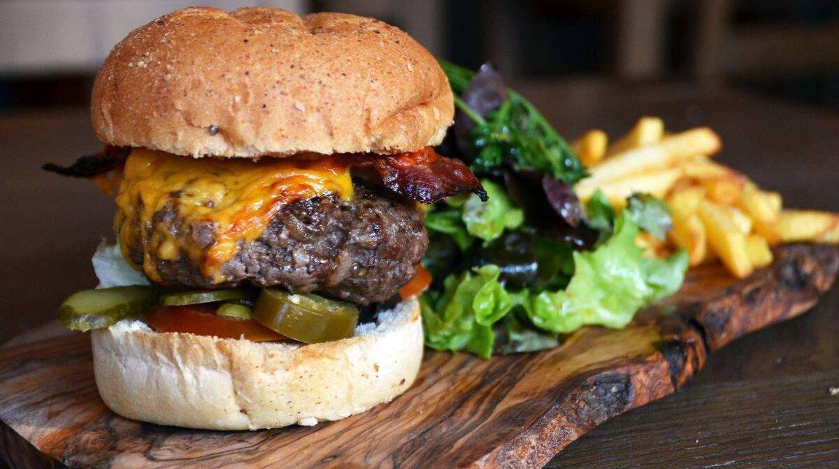 a burger on a wooden platter