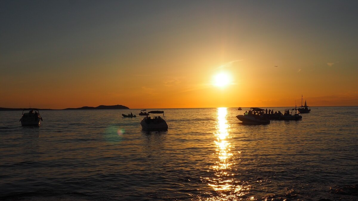 boats floating in the water off san antonio as the sunsets in ibiza