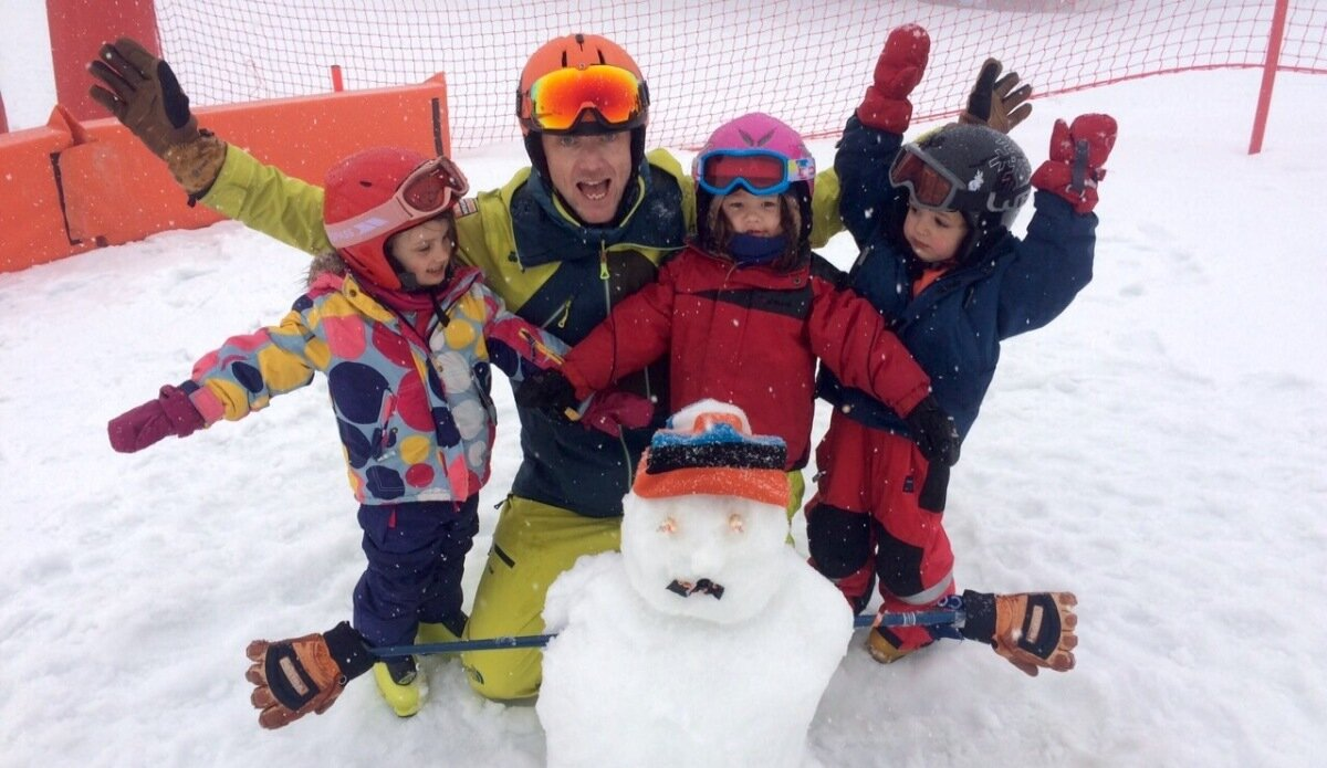 children with a ski guide & snowman