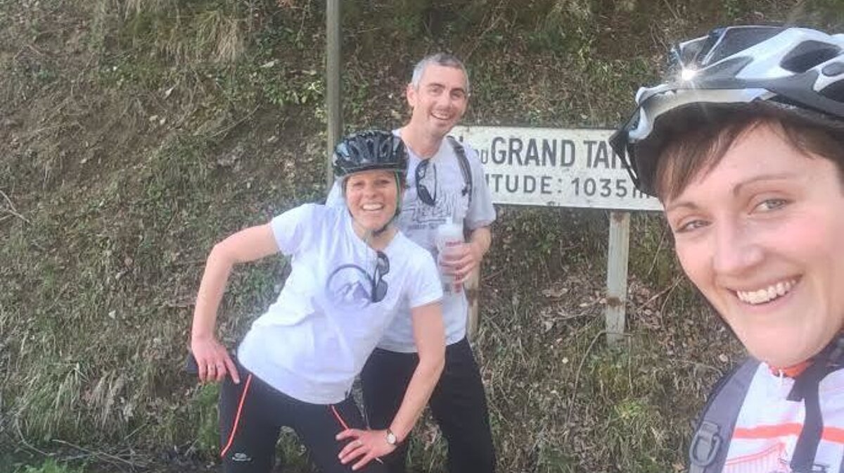 three people by a sign on a road bike climb