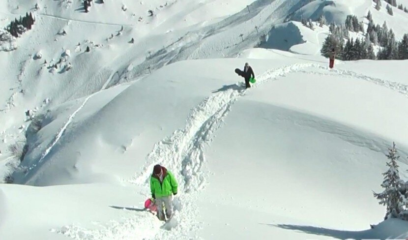 an image of snowboarders hiking