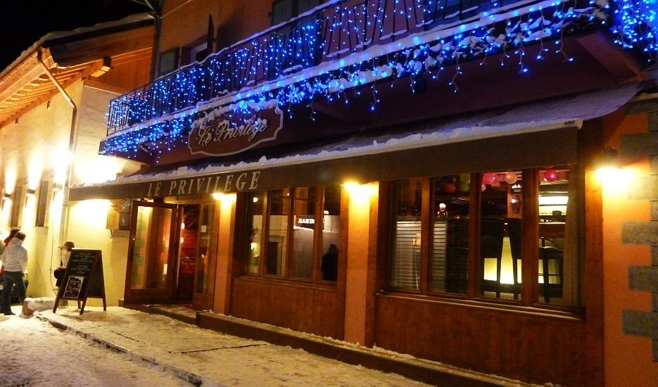 An image of a Le Priviliege apres-ski bar on a snowy street in winter in Chamonix Mont Blanc