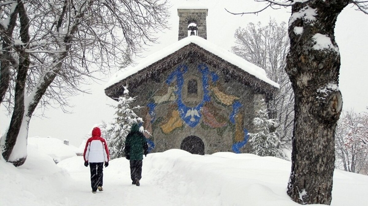 two walkers in the snow going towards a church